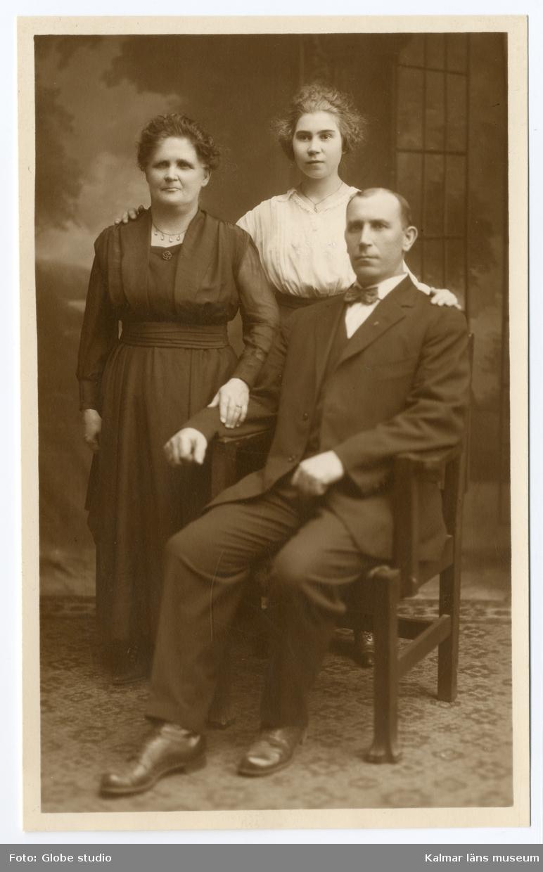 Familjeporträtt? Till vänster står en mörkhårig kvinna klädd i svart klänning.Till höger om henne står en yngre ljushårig kvinna, klädd i ljus blus. Längst till höger sitter en man på en stol, han är klädd i mörk kostym.
