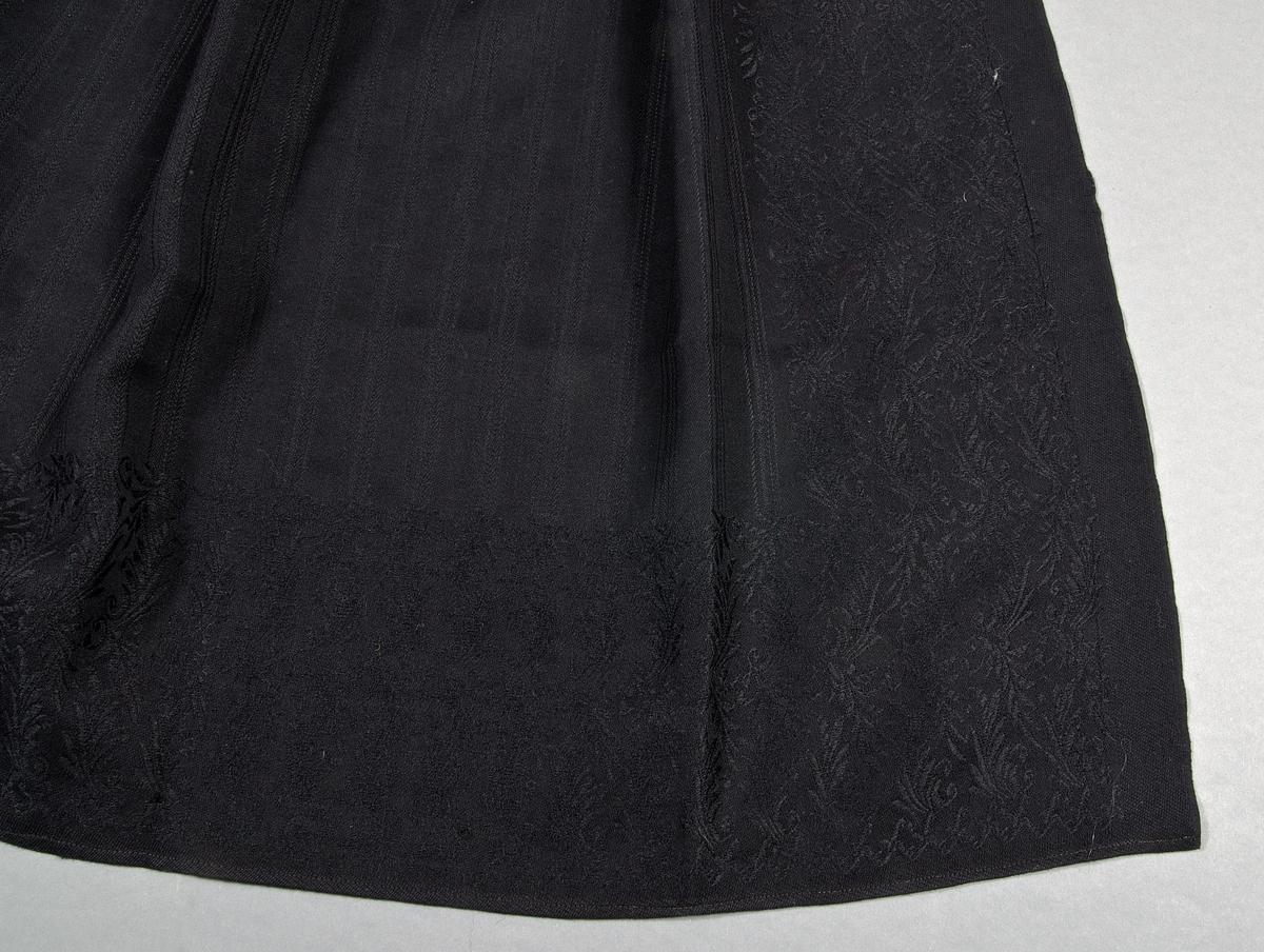 Svart förkläde av maskinvävt ylletyg, med ränder och bårder på tre sidor. Maskinsytt med ljusbrun tråd.  Slitageskador, framför allt på förklädets kanter. Ett hål mitt på förklädet.