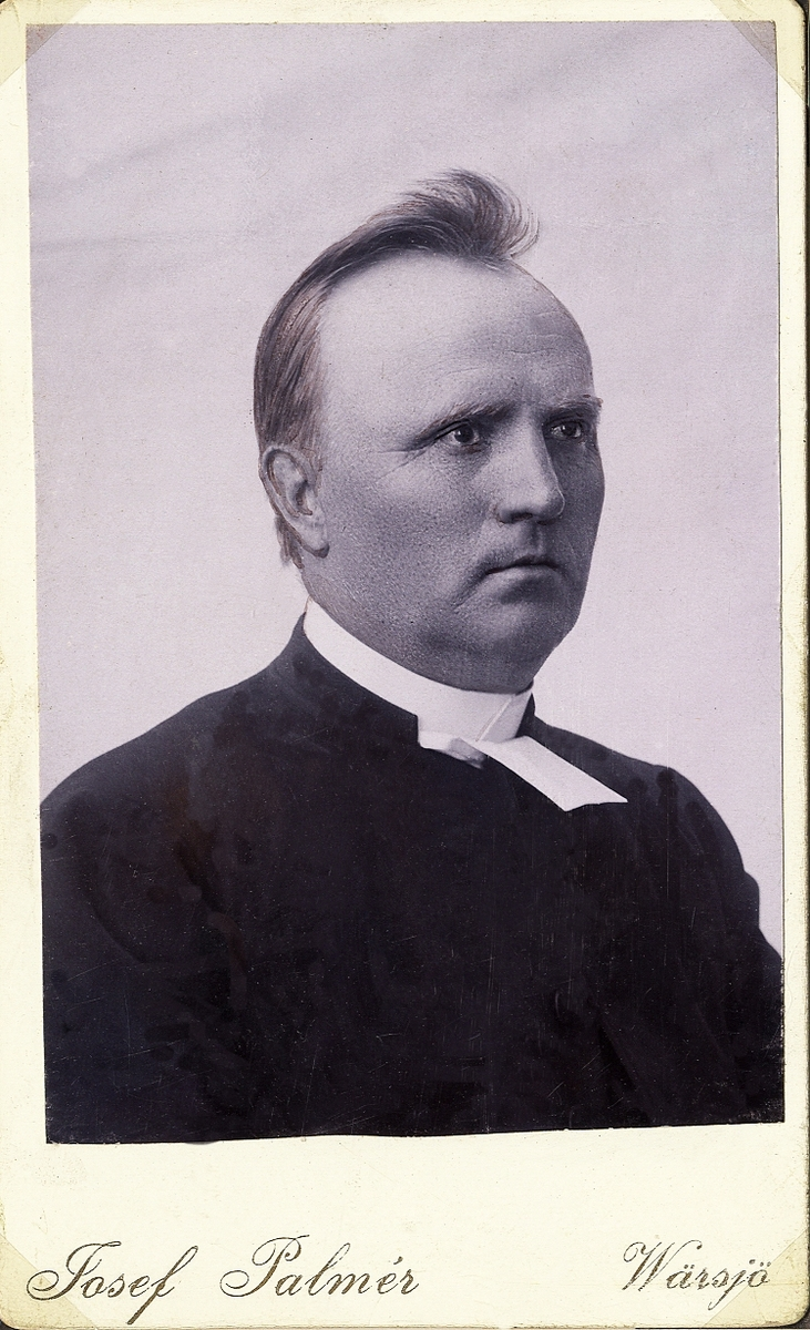 Foto av en man i prästrock och prästkrage,  Bröstbild, halvprofil. Ateljéfoto.