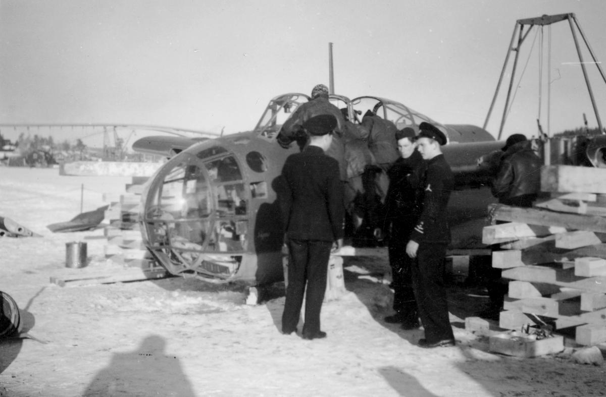 Flygtekniker och flygvapenpersonal samlade vid bärgat flygplan B 18 på kajen i Härnösands hamn efter nödlandning på isen den 10 februari 1946. Motorerna har demonterats. I bakgrunden syns en lyftkran som användes vid bärgningen.