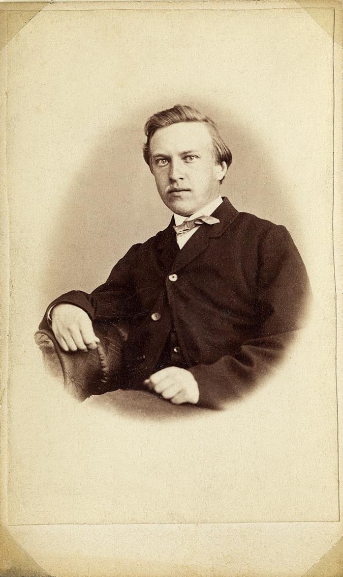 Foto av en man klädd i kavajkostym med stärkkrage och fluga.  Midjebild, halvprofil. Ateljéfoto.