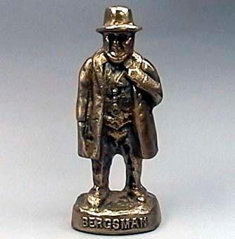 """Statyett i mäswsing föreställande en man i bergsmansdräkt. Titeln """"BERGSMAN"""" står på sockeln. Symboliserar tillsammans med  """"BERGSMOR"""" Järnvägens vagga i Sverige"""
