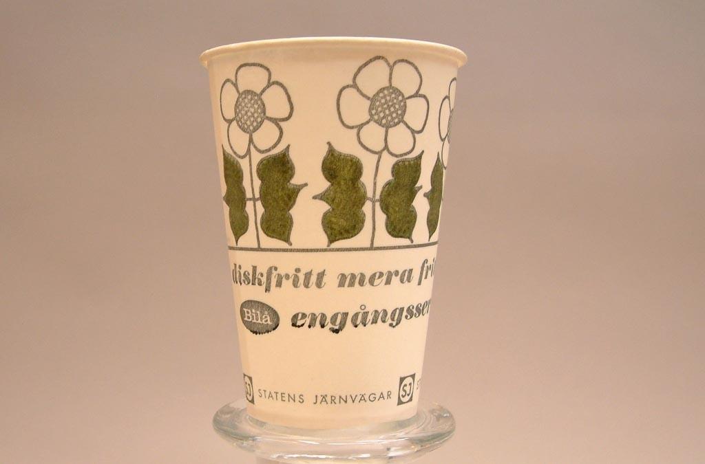 """Vit pappersmugg. med olivgröna blad och gröna och vita blommor. Text """"engångsservis"""" Statens Järnvägar med SJ-logga."""