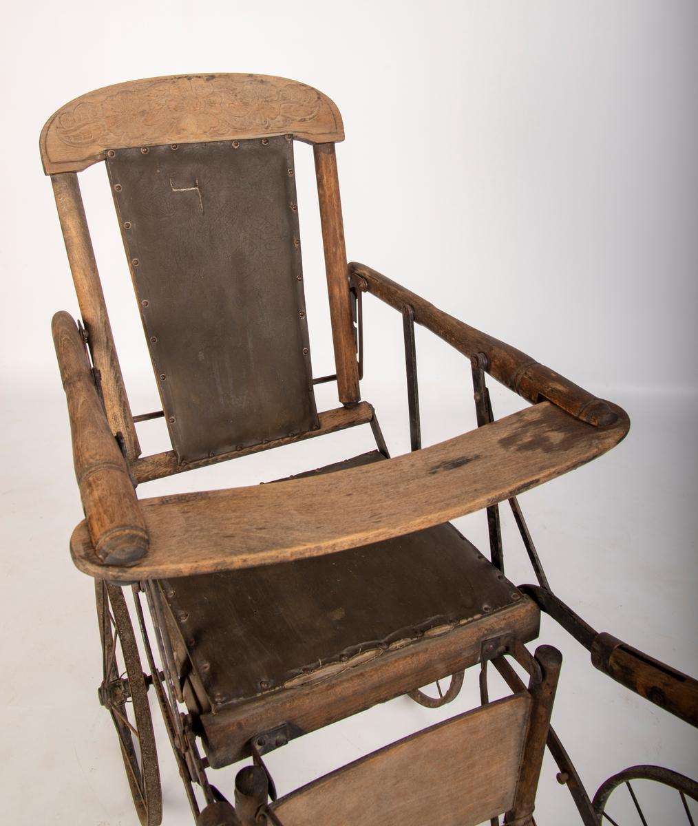 Ramme av tre med kunstlær i sete og rygg. Håndtak av jernrør. 4 hjul mangler dekk. Mangler stopper for fotbrett. Hull i ryggtrekket og mye rust. Setetrekket løsnet i den ene siden. noen enkle reparasjoner med ståltråd.