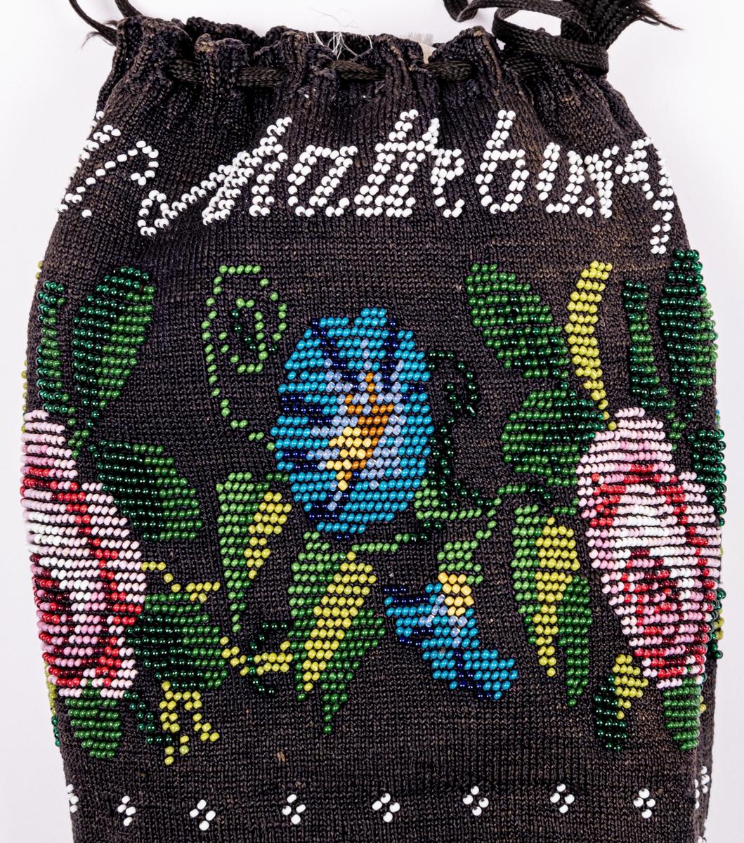 Väska i påsform, svart garn, pärlstickad med små glaspärlor i blommönster, vit pärlbård, märkt med vita pärlor: H. W. Schatteburg, 1831.