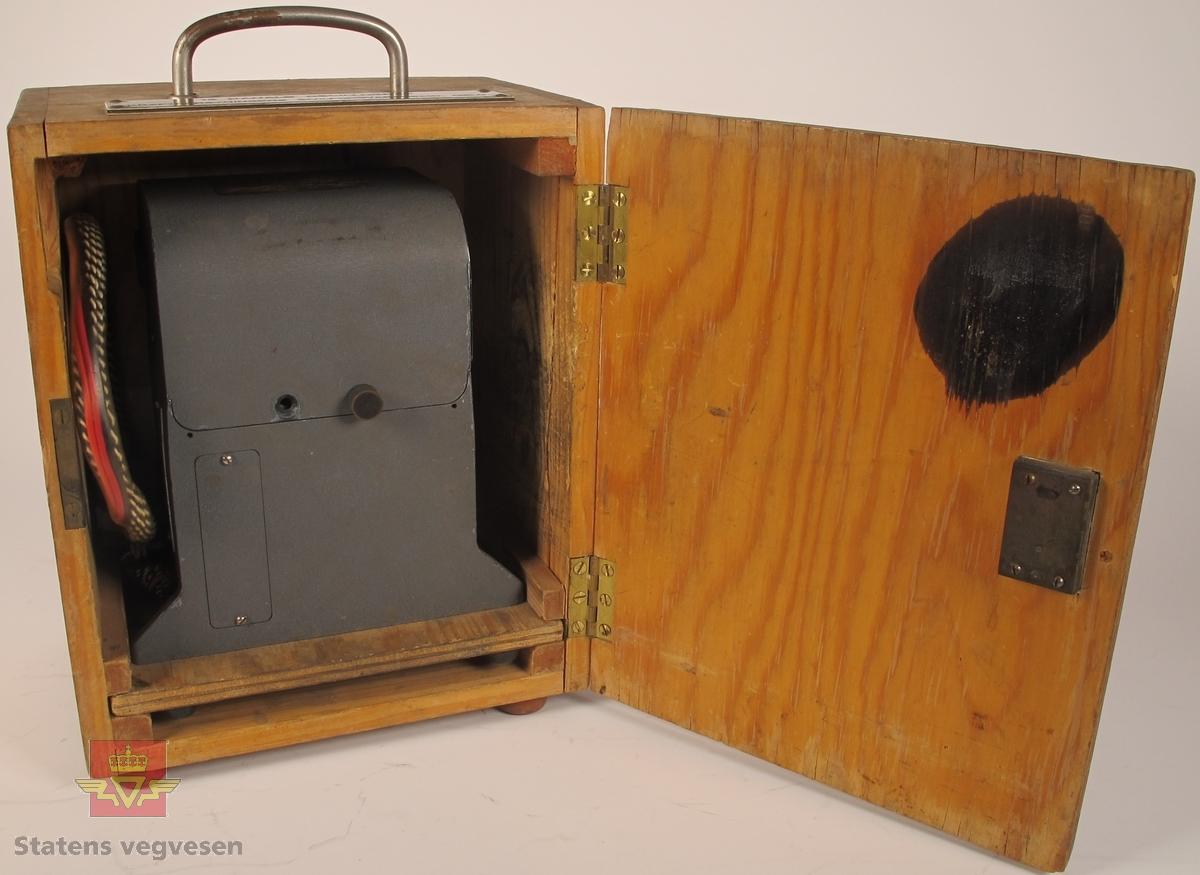 Oscillograf i oppbevaringskasse av treverk, med bærehåntak og låsekasse med nøkkel. Oscillografen er i grålakkert metall med skiltplate som har innskriften MIDWESTERN INSTRUMENTS MOD. 560 SER. 543 DATE 8 - 58 TULSA, OKLA. U. S. A. Den har utgående ledninger som er samlet i en gjennomsiktig gummistrømpe, og i enden sitter det en kobling i plast med 12 tilkoblingspunkter. Klistremerke på toppen med håndskriften Film i kassetten 28/4-64. Oppbevaringskassen er merket med skilt som har innskriften 12 KANALS OSCILLOGRAF KRAFTFORSYNINGENS SIVILFORSVARSNEMD, OSLO. Inni oppbevaringskassen ligger et papirark med håndskrift der det er skrevet ned når det er satt i ny film, og hvor mye film som er benyttet ved bruk, og hvor mange meter som gjenstår.