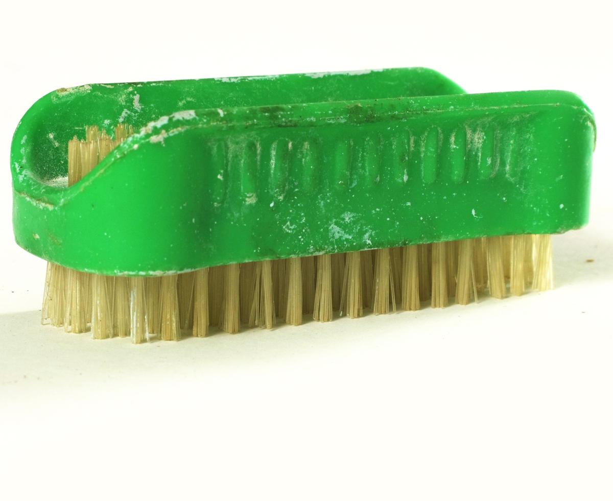 Neglebørste av grønn  plast, bust av hvit  nylon. Langbust på undersiden av håndtaket, kortbust i U formet fordypning på oversiden.