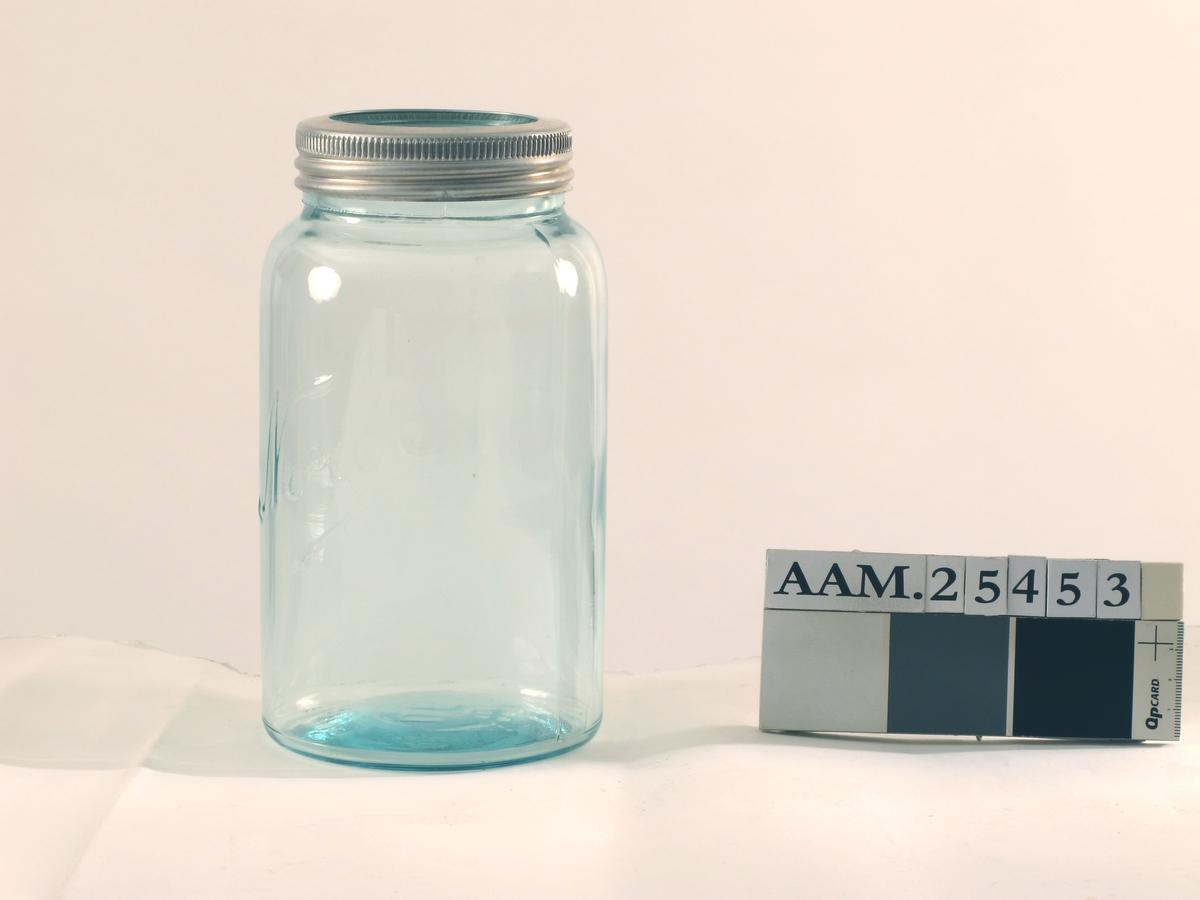 Glass med lokk. Sylindrisk form, avsmalnende mot lokket. Lokk av glass, med skrulokk av aluminium. Opprinnelig med gummipakning.  a) Glass  b) Glasslokk  c) Skrulokk av aluminium