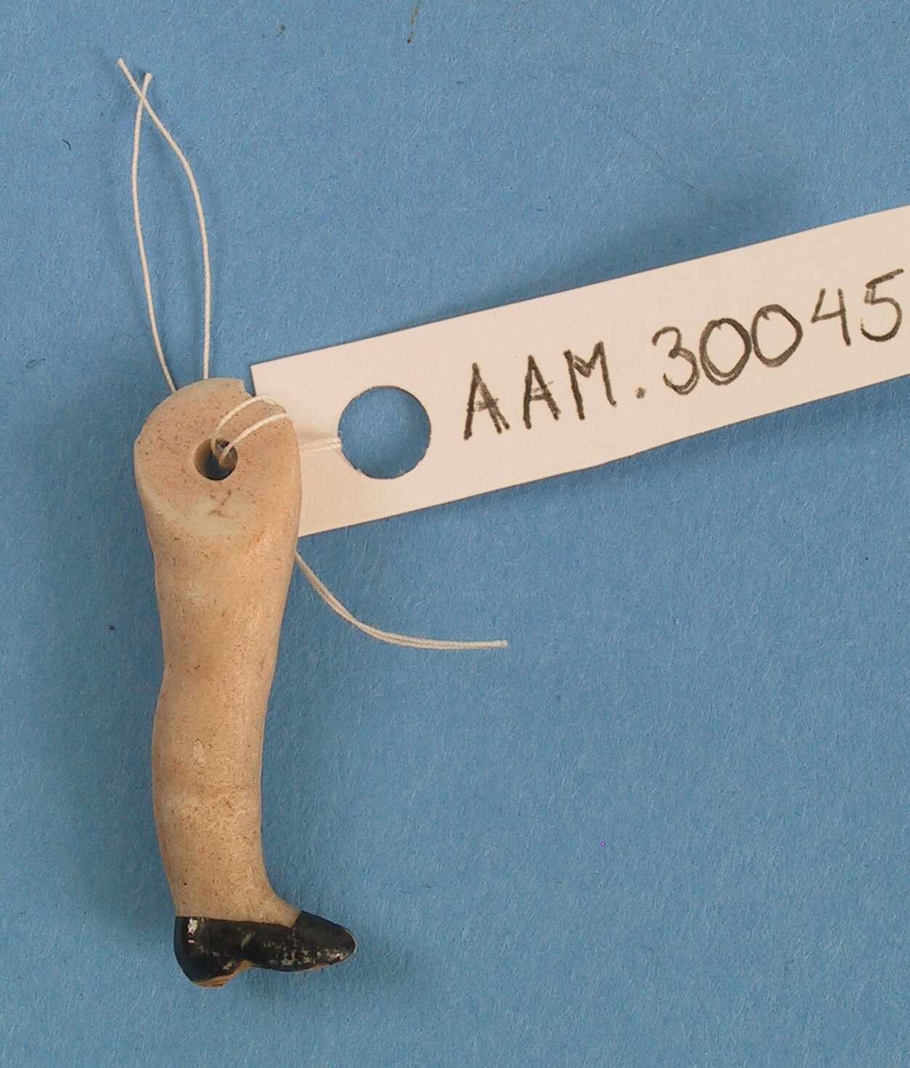Form: Lite dukkeben med påmalt sko.