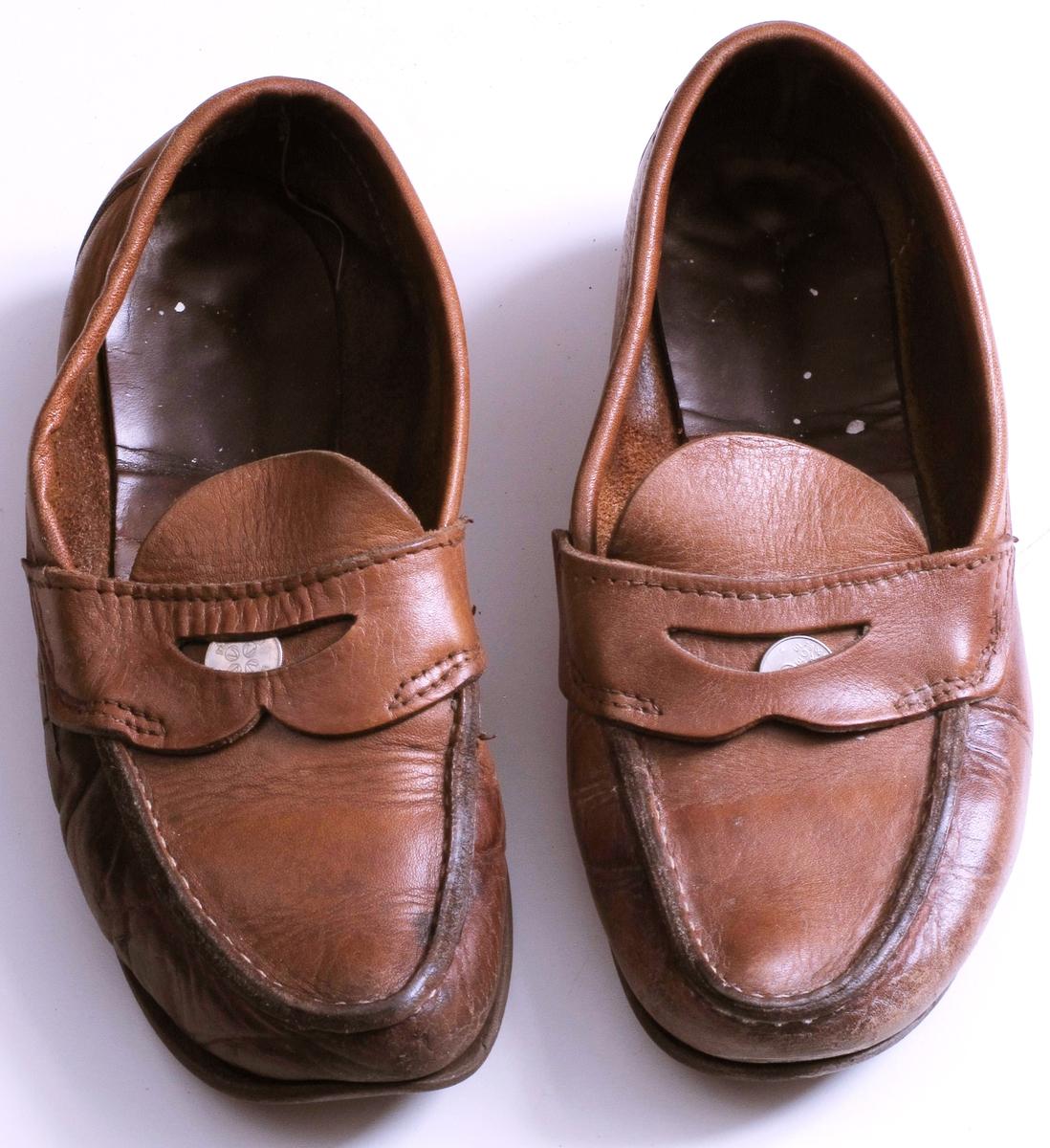 Brune makkasiner i lær, med brune gummisåler.  Lomme foran med 25-ører i.  Høyre sko har en metallstift i sålen rett foran hælen.  Velbrukte, høyre sko er gjennomslitt på utsiden av foten, og med malingflekker oppi.