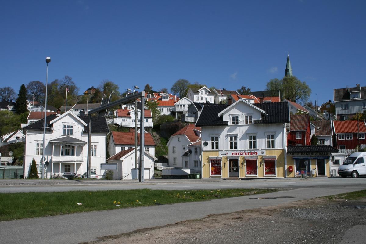 De sentrale bygninger i strandstedet Barbu, den gamle lensmannsgården t.v. og grosserer Thorsens hus t.h. I forgrunnen gang og sykkelvei langs Kystveien. Hit gikk Barbubukt til den ble gjenfyllt i 1970-tallet.