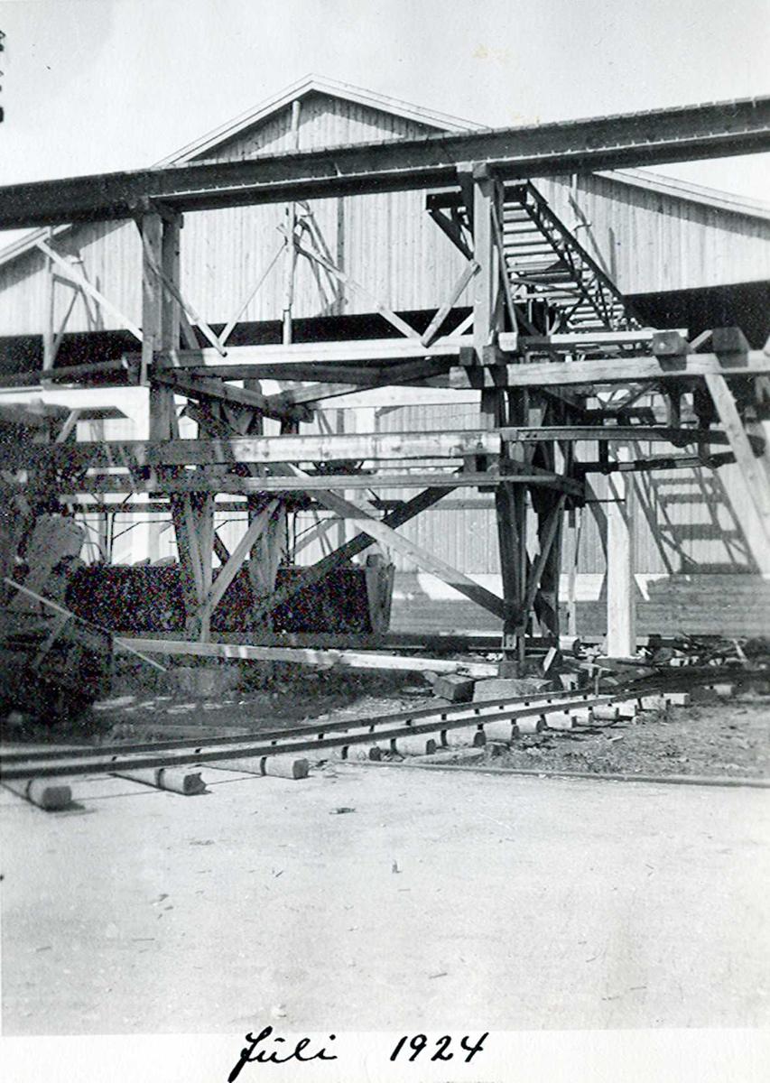 """""""xx/07-1924"""" Nitriden. Taubane endestasjon på kai. Skinner for taubanevogner. Skinnegang for traller på bakkenivå, med skinner og sviller. Lagerbygning i bakgrunnen."""