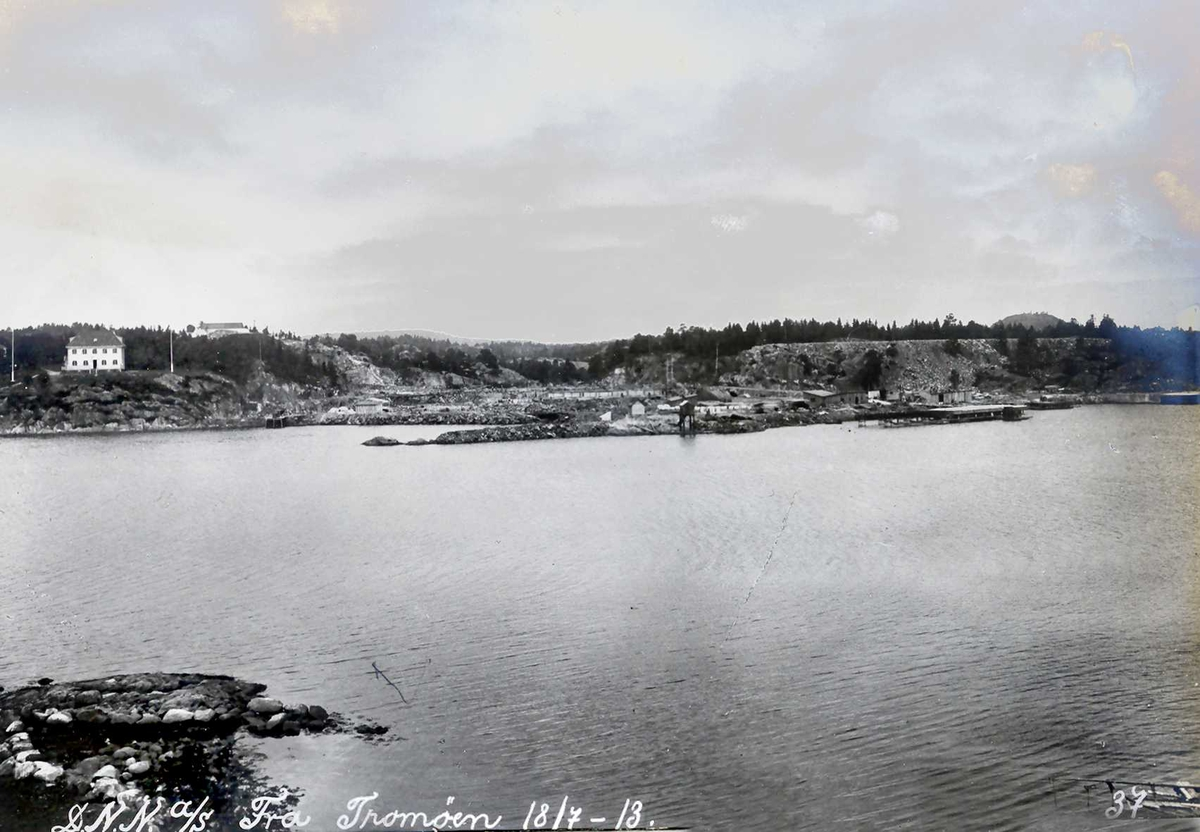 """""""18/07-1913"""" Nitriden. Fabrikktomten, planert, sett fra Tromøy. Til venstre Smelteverkets direktørbolig, høydebassenget for trykkvann. Til høyre tomt for svovelsyrefabrikken som ikke ble noe av. Midt på bildet fyrlykt nr. 612 i Norsk Fyrliste, bygd 1894, flyttet til Friisøy i 1929. Kaianlegg til høyre. Tromøysund i forgrunnen."""