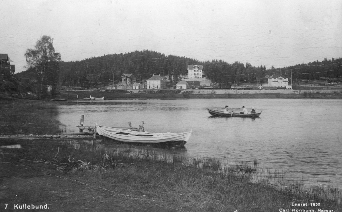 Båt ved brygge på Kolbotntjernet, tre mennesker i robåt. Kolbotn stasjon i bakgrunnen (postkort)