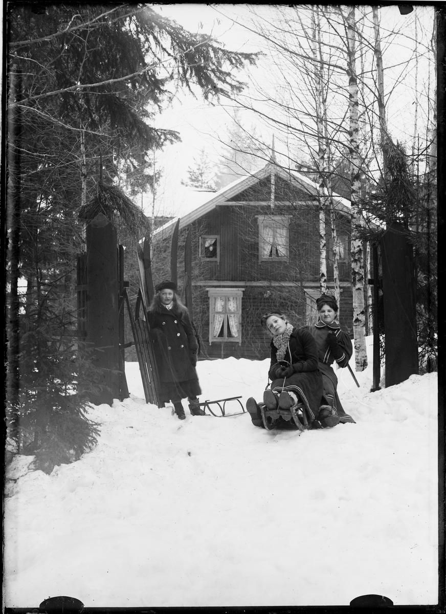 Jenter med kjelke utenfor huset. Gudrun Grann-Meyer med venninde og guvernante.
