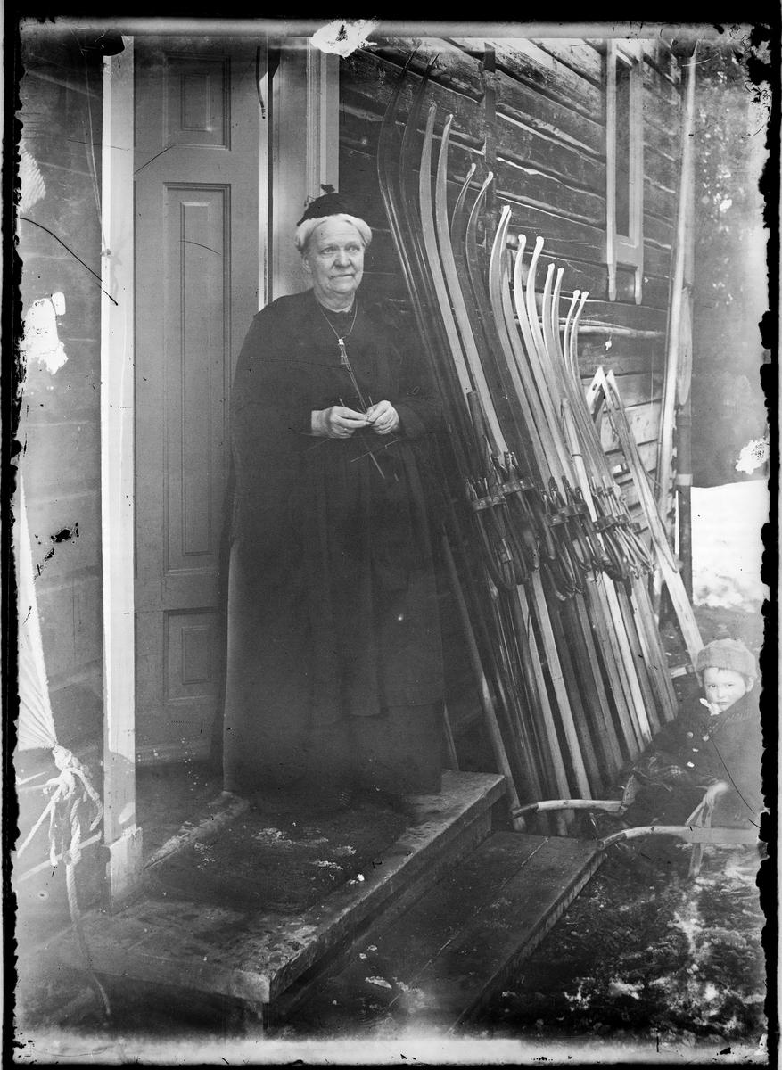 Bestemor Emilie Meyer ved bakdøren. Ski inntil husvegg.