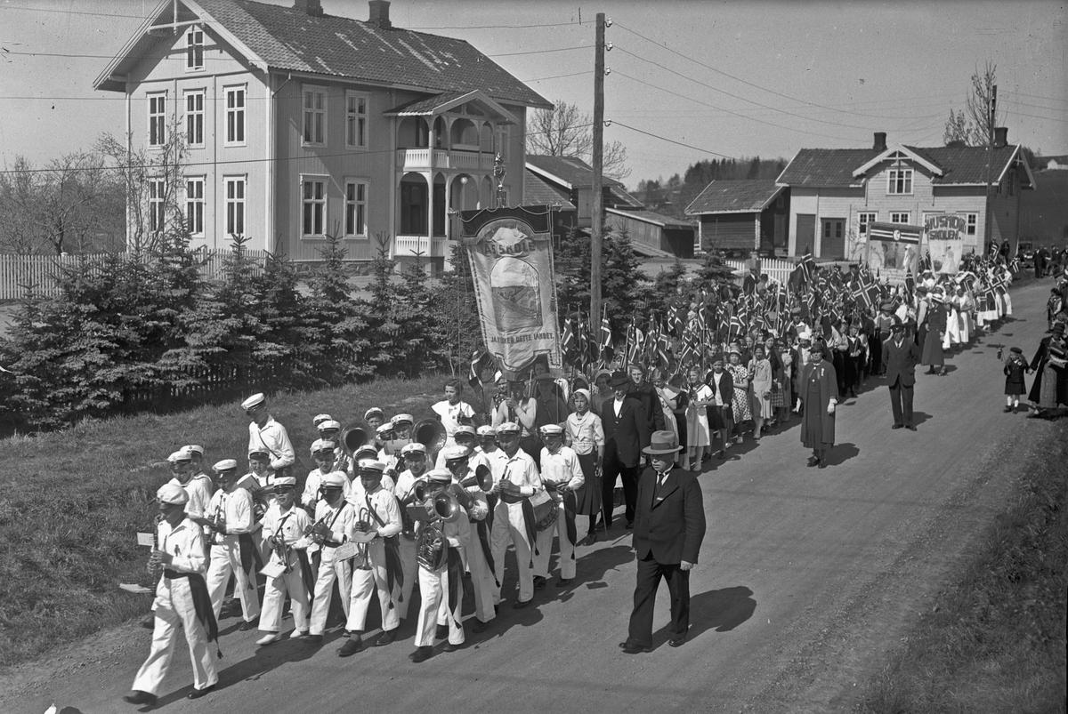 17. mai tog med korps. Faner fra Ås skole og Husmorskolen.