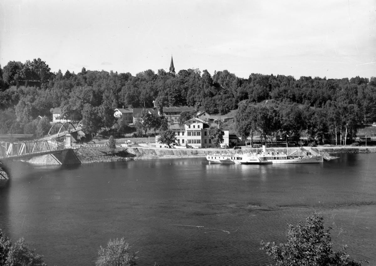 Eidsvoll stasjon med Skibladner foran. Fyllingen foran stasjonen ble laget like etter krigen. 3 jernbaneboliger bak stasjonen og nesten helt skjult bak ligger Hoels hospits eller pensjonat/hotell.