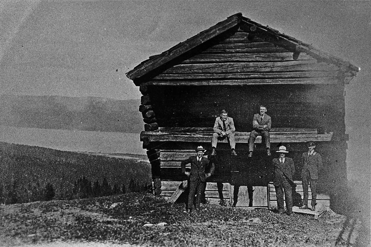 Menn utenfor en tømmerbygning