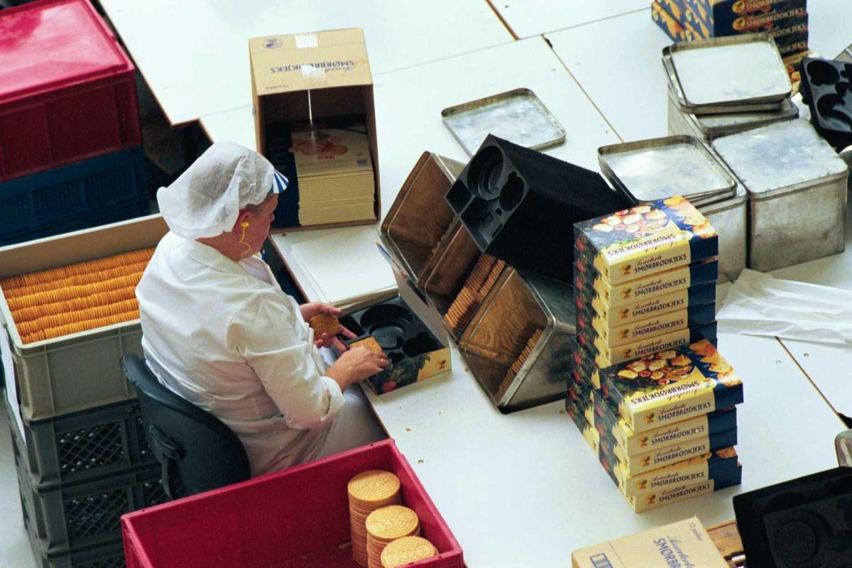 Håndpakking av kjeks, arbeidsmiljø, hørselvern, arbeider, kvinne, emballasje, fabrikkmiljø