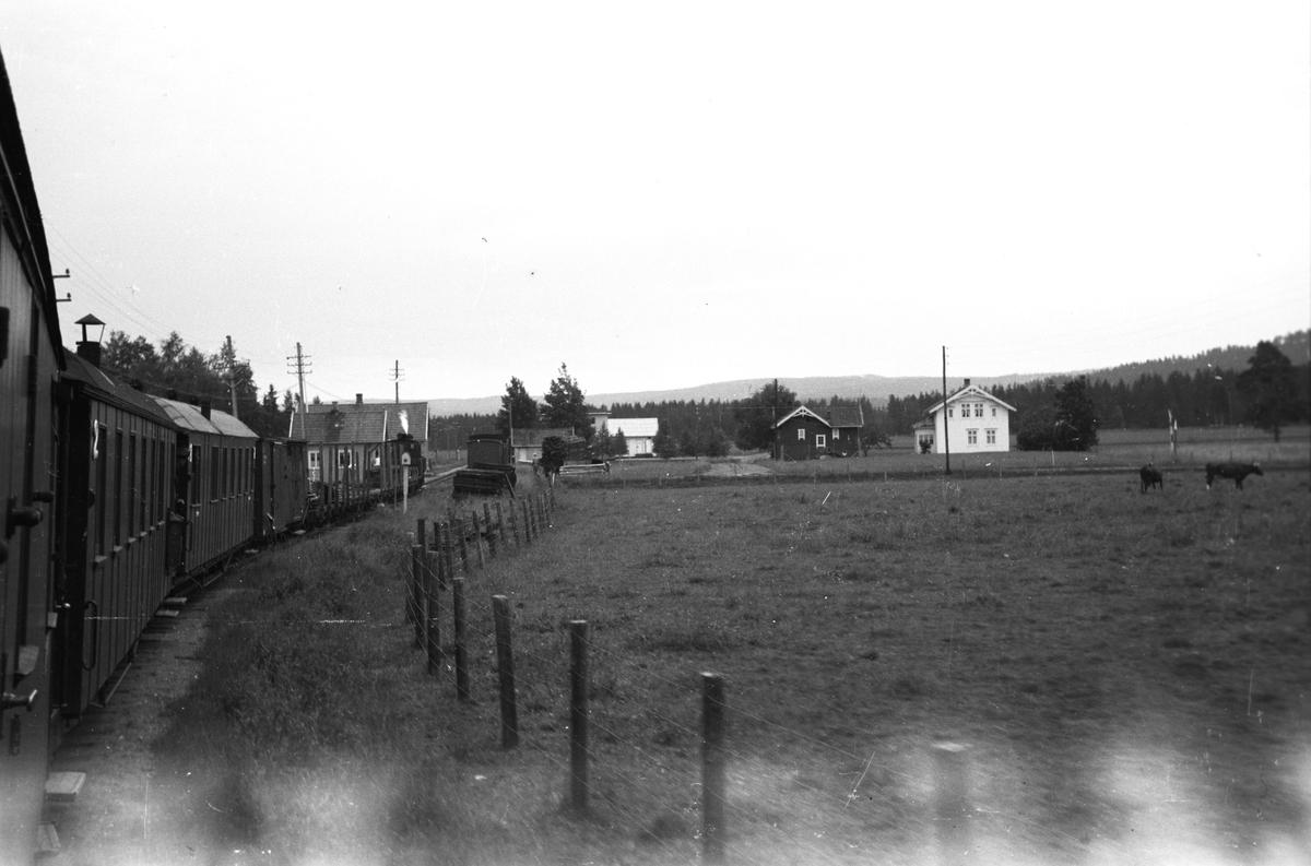 Tog 2051 retning Skulerud. Ved innkjøringen til Mork stasjon. Mork meieri i bakgrunnen midt i bildet. Lok 7 Prydz, Vogn To53 (?),  ..., ..., ..., G57, G7, BCo4, BCo3 og CFo5. Løftekasse 231.