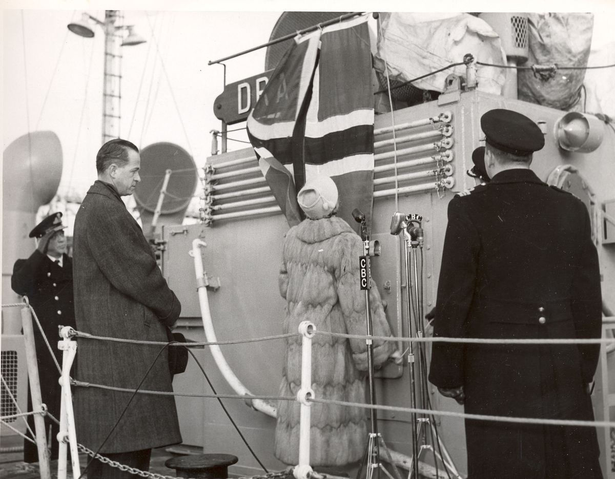 """Overtakelsen av River-kl.fregatt KNM """"Draug"""", ex. HMCS Pentang. Admiral S. Storeheil, , ambassadør A. Gunneng, fru Gunneng som avduker skipes navn, og skipssjef E. Zachariassen."""
