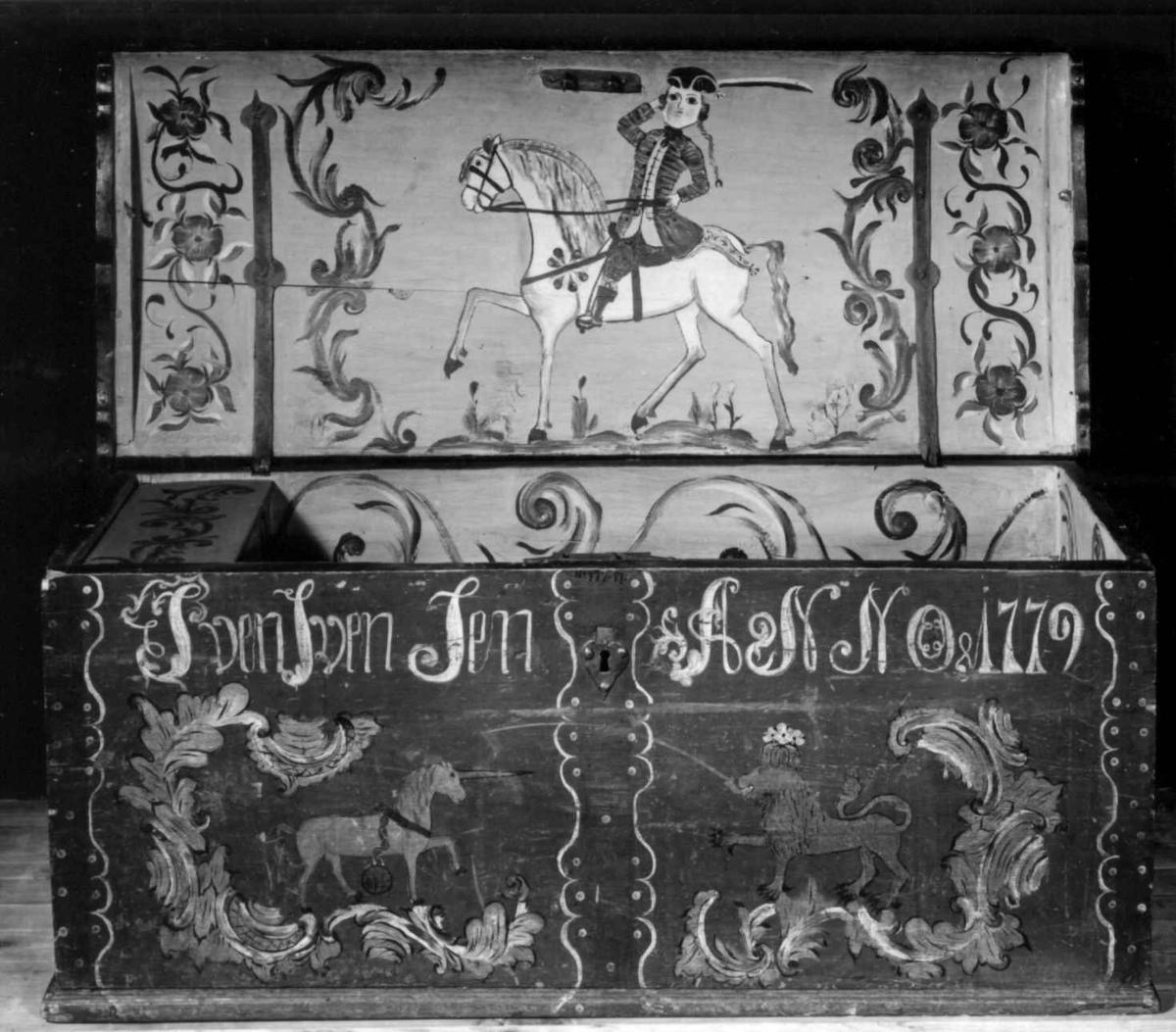 Kiste med svakt buet lokk og påmalte figurer og rokokkoornamentikk.