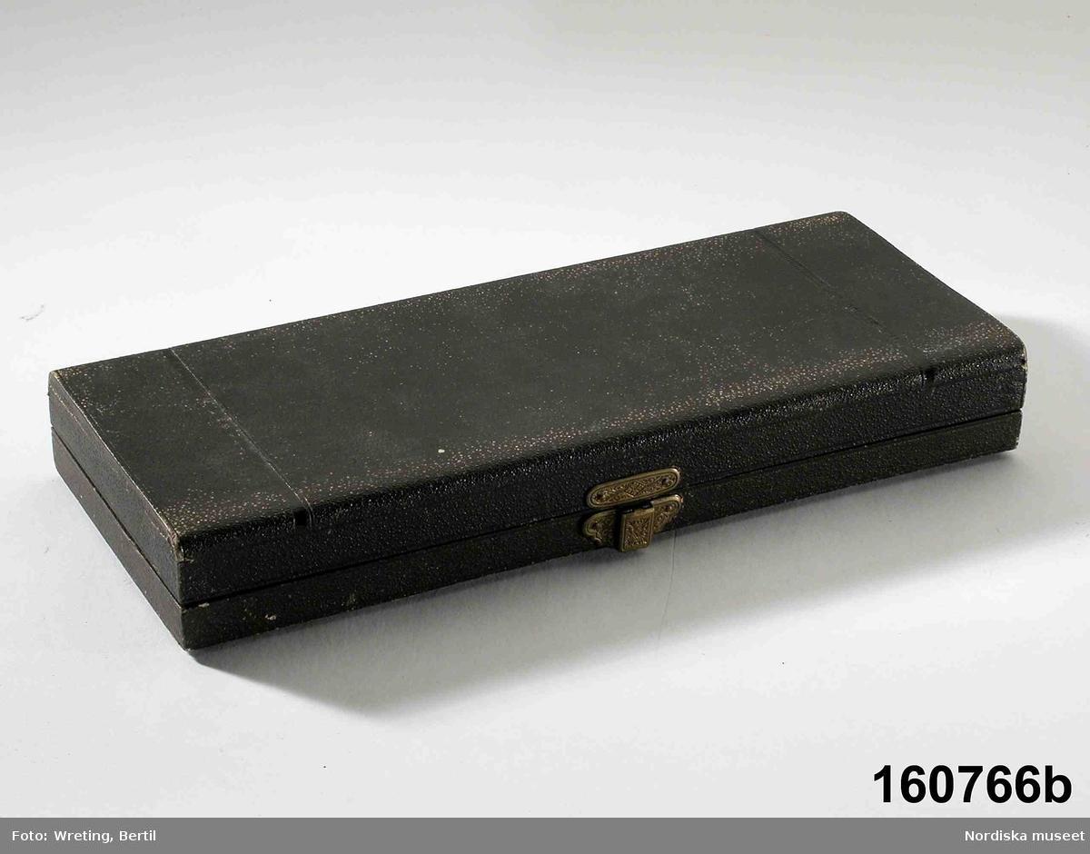 """Huvudliggaren: """"Halssmycke av silver, förgyllt, sammlänkade bucklor med filigranornering, den största löstagbar till brosch. Stämplad '(tre kronor) / AGM / D6 (=1882) / s:t Eriks bild'  Halsband av förgyllt silver i form av halvklotformade fligransdekorerade delar med en större sådan hängande mitt fram. Stämplad se ovan. Tillverkad av Gustav Millberg 1882. Intresset för fornnordisk historia och för allmogekultur resulterade i bland annat den här formen av smycken. Ingrid Roos 2008-01-14"""