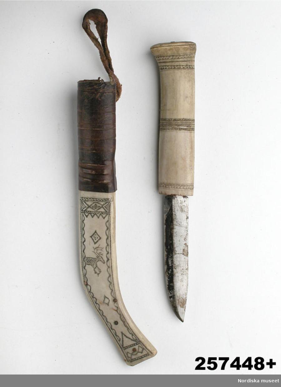"""Huvudliggaren: """"+ Kniv med renhornsslida, knivskaft av ben med enkel bandornering, slidan av två hopnitade renhornshalvor, på framsidan ornering i svart, band- och randornering samt en ren, upptill läderhylsa med läderögla, på baksidan ristat: O. Olsson / Abesko 11.4.28'. L 29 cm. G[åva] 17/3 1959 [av] Fröken Ingeborg Ulff, Stockholm. [Brukningsort:] Lappland Jukkasjärvi sn."""""""