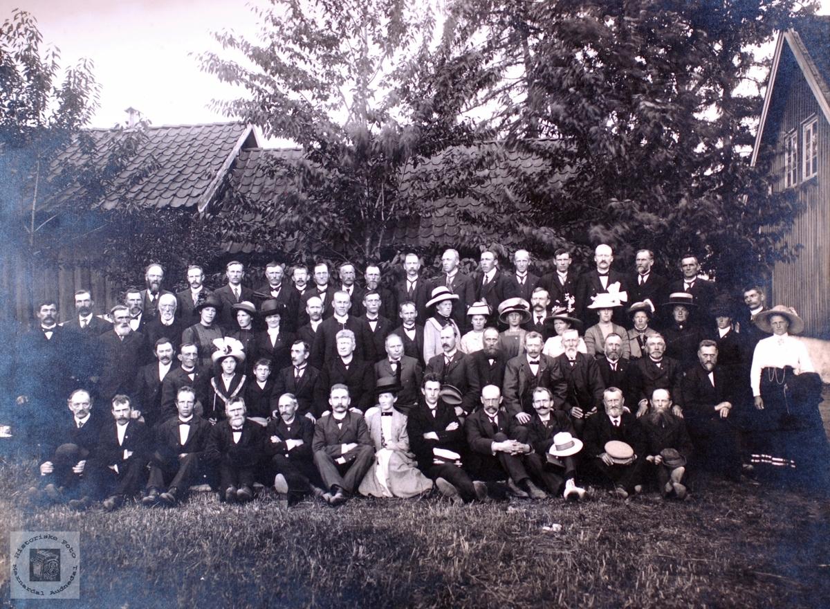 Portrett av stor gruppe med hus og uthus i bakgrunnen.
