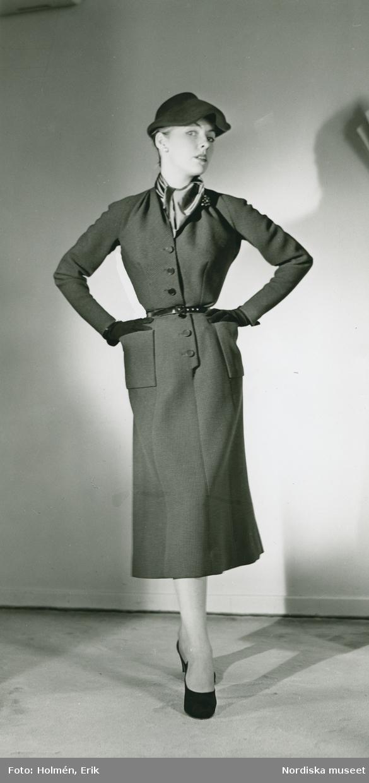 """EM """"Modellbutik"""" Nordiska Kompaniet, Damkonfektion. Modell i klänning med skärp och sidenscar , hatt, handskar och pumps. Från Christian  Dior."""