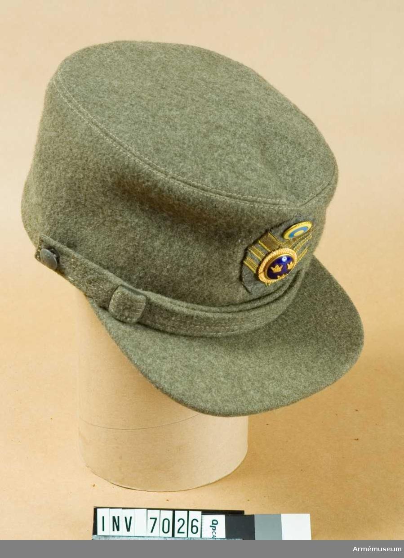 I kommisskläde med överklädd skärm och rem i samma material. Nedvikbart skydd för panna, nacke och öron. Mössmärke, ovalt, mjukt i kommisskläde med gradbeteckning för ölt i guldgalon. Knapp för officer m/1865 och halmkrans m/1833 och neutralitetsmärke m/1941. Mössmärke m/1952. Bärs till uniform m/1939 och 1952.Storlek 55, färg Q O P, tämligen gott skick, bruten skärm.