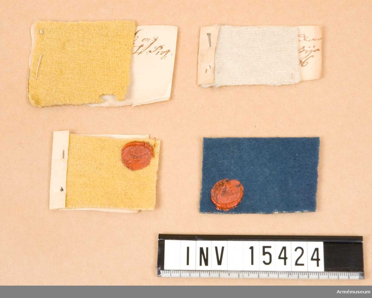 """Grupp C III.  Ett prov av vit boj, två av gult kläde och ett av blått kläde. Proverna är fästa vid papperslappar med text. Två av dem är försedda med lacksigill. Att de är kontrollbitar tagna vid avsyningen av en tygleverans framgår av en av texerna: """"Prof af Packen No 40 och stycket No 1206"""". Proverna kommer troligtvis ur Beklädnadskontorets liggare över 1701 och 1702 års tygleveranser från England som förvaras i Krigsarkivet.  KTS 2013-01-30"""