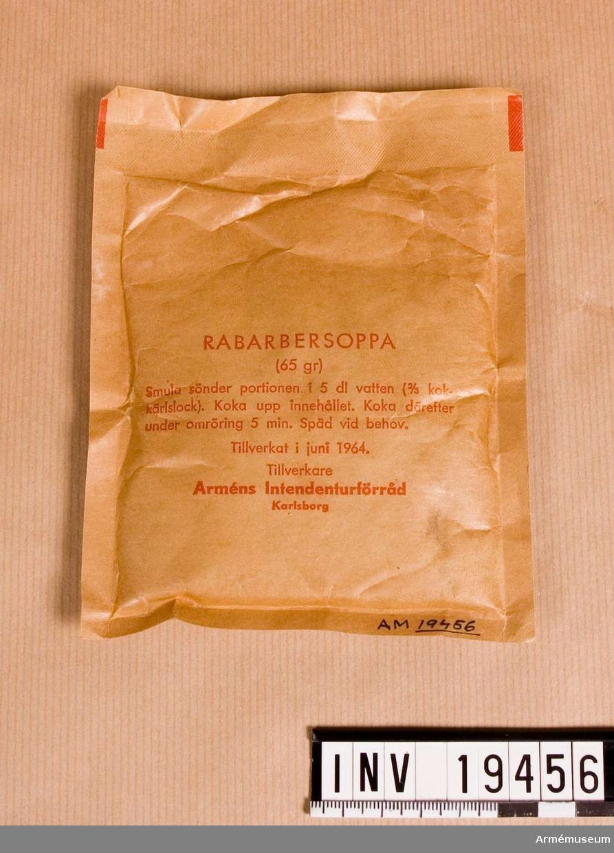"""Pulvret finns i en tillsluten brun påse med text """"RABARBERSOPPA (65 gr) Smula sönder portionen i 5 dl vatten (2/3 kok- kärlslock). Koka upp innehållet. Koka därefter under omröring 3-5 min. Späd vid behov. Tillverkat i juni 1964 Tillverkare Arméns intendenturförråd Karlsborg"""".  Samhörande nr AM.19450-7"""