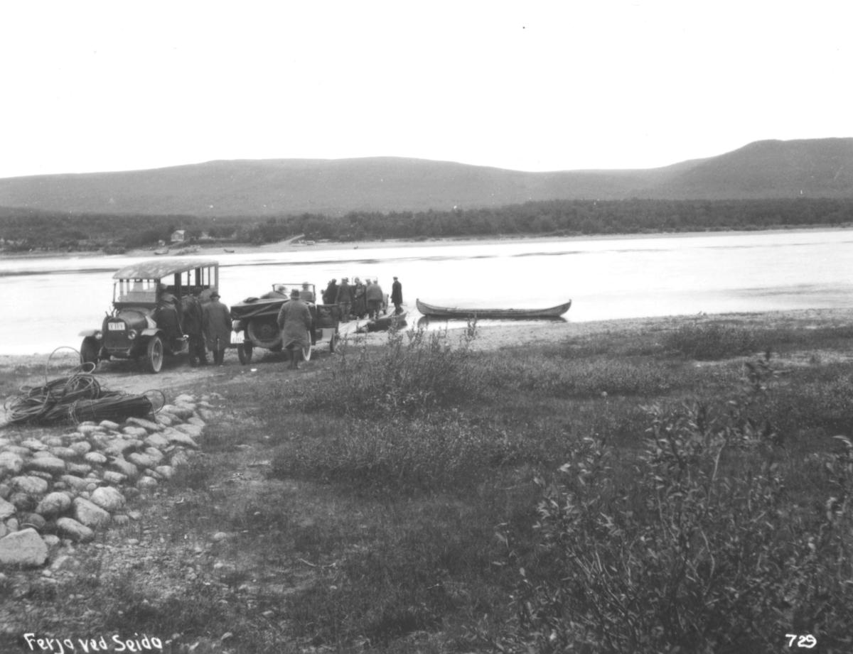 Jernbanekomiteens medlemmer med tre biler ved tau-fergeleiet i Seida ve Tanaelva. Til venstre en høyrestyrt Opel 30hk med registrernummer Y-114, eies av A/S Polarbil. Videre en personvogn National med registrernummer Y-120, eies av Sigbjørn Aarnes fra Vadsø. I 1939 ble det bygt broa her.