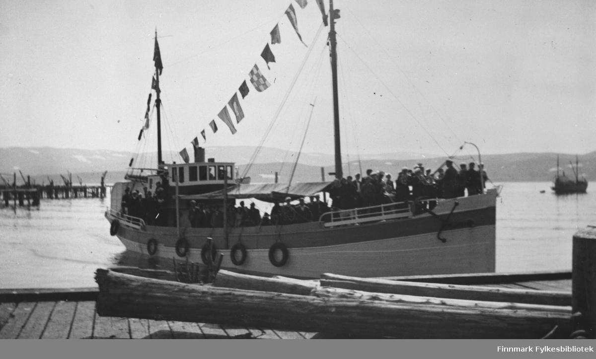 Berlevåg Mannskor på turne 1936. Her er de på vei til en konsert som NRK Vardø sendte over den lokale Kringkastinga. (hørtes så langt som til Bodø) På bildet her er Mannskoret ombord i en hvit båt ved Guldbrandsenkaia i Kongsfjord. Helt framme på akterdekket står folk å spiller på blåseinstumenter. Båten er pyntet med flagg og vimpler. Midt på båten er det laget til et tak av en pressening som folk kan stå under.