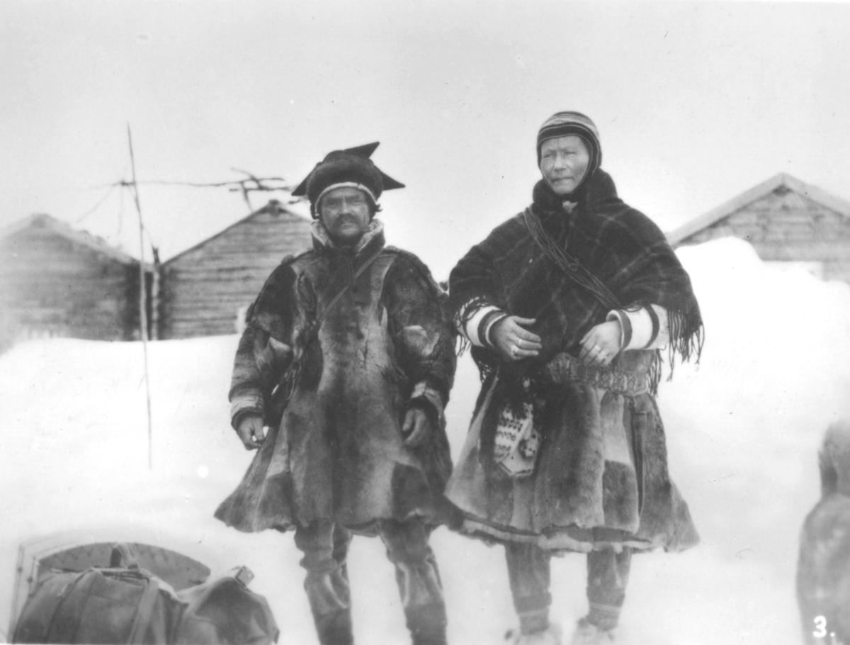 Bilde nr. 3 i serien '10 amatørbilleder fra lappernes hjem og liv i Finnmark', se FB 93164-001. 'Et finnepar fra Kautokeino.'  En kvinne og en mann ute i snø. Hus i bakgrunnen. De er kledt i pesk. Han har stjernelue, veske over skuldra og skinnbukser. Hun har sjal, lasso, skinnbukser, skaller og strikkavotter.