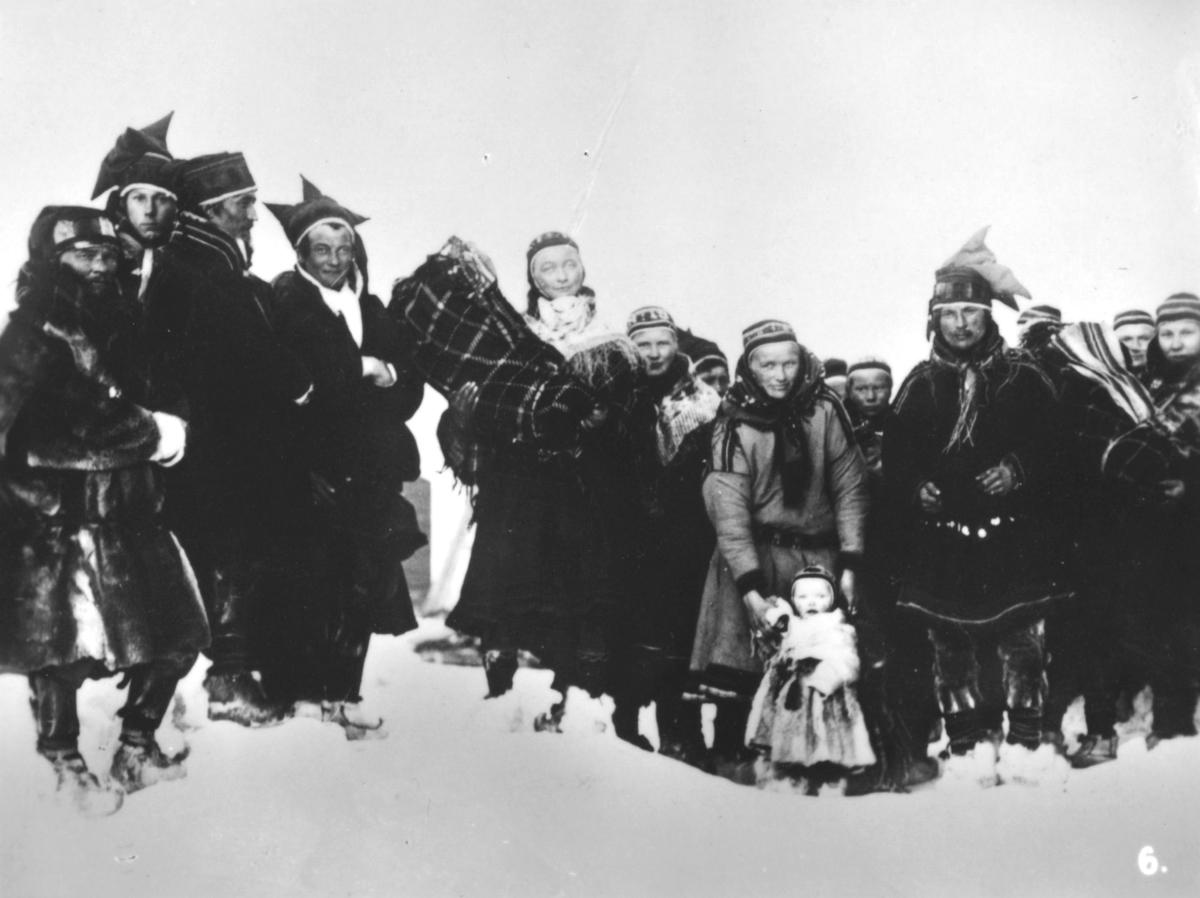 Bilde nr. 6 i serien '10 amatørbilleder fra lappernes hjem og liv i Finnmark', se FB 93164-001. 'Lappebarna bringes til kirke for at døpes.'  En gruppe samer kledt i pesker og kofter. Menn med stjerneluer, kvinner i luer og sjal. Skaller på beina. To barn ligger i komse, et barn står foran, kledt i pesk.