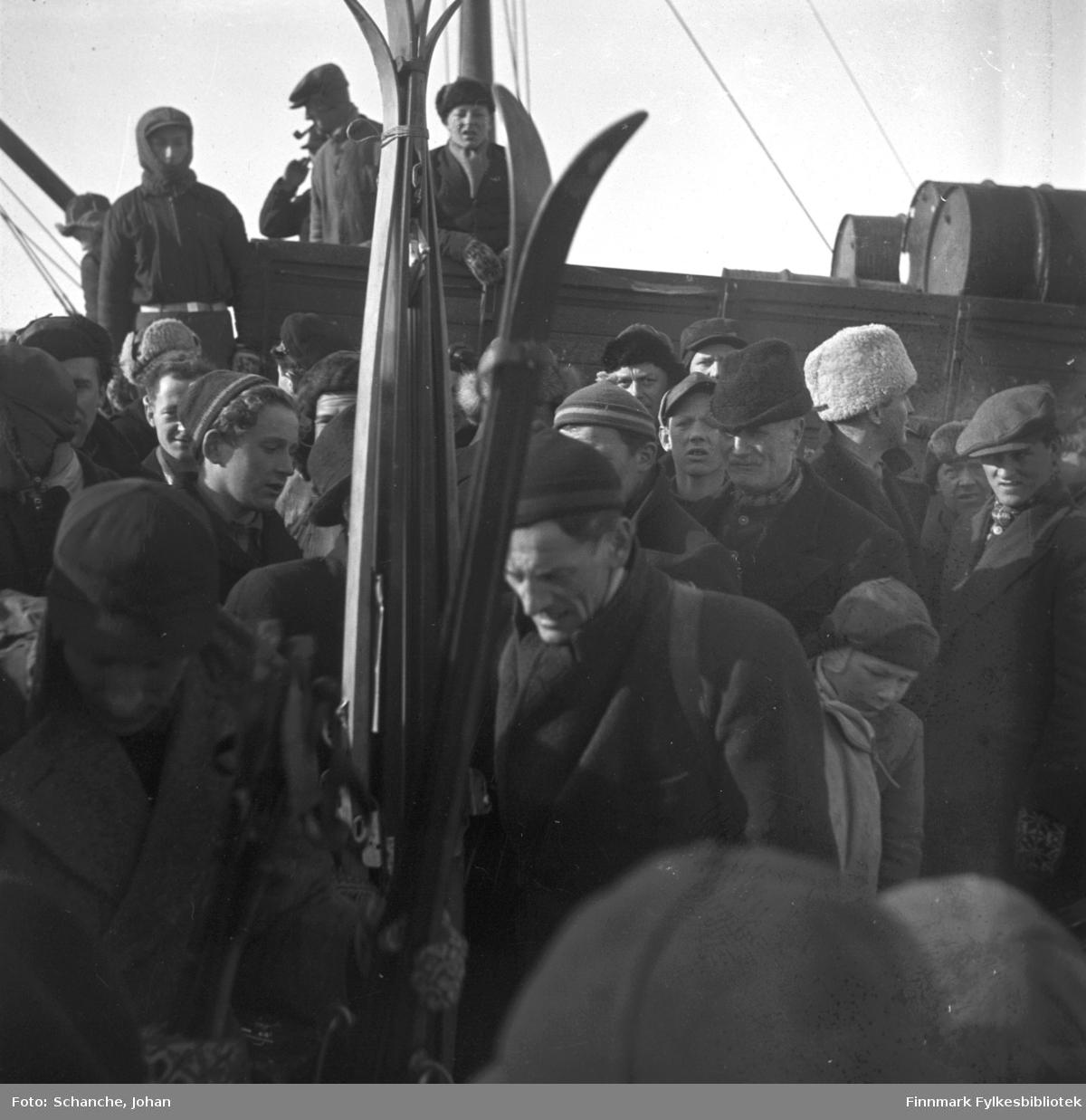Fra kretsrennet i Vadsø 1946. Olav Odden ankommer Vadsø for å delta. Vi ser han midt på bildet, bak noen skipar. Det er flere på bildet. De er kledt i luer og skjerf.