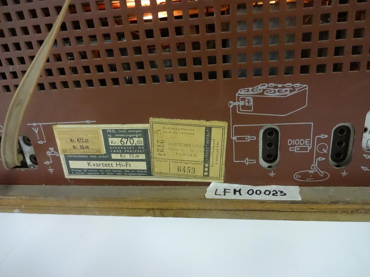 """Radioapparat fra Radionette. Har fire ratt: volum, tonekontroll, bass / diskant og stasjonsvelger. Knapper for valg av båndbredde. FM-radio og egen knapp merket """"F"""" for fiskeriradioen. Radioen har merker på baksiden som forteller at den ble solgt av Radiocentralen i Bergen, kostet 670 kr og hade en stempelavgift på 55 kr. Apparatet fungerer.  Det er og mulig å koble ti båndspiller / grammofon."""
