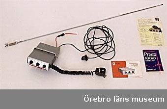 """1) Kommunikations-radio """"MESSENGER 110"""" av grå metall med plast delar. 3 sökknappar (svart, hårdplast)  på framsidan. Fastmonterad mörkgrå spiralsladd med mikrofon på hö sidan. Extra lång - 4500 mm - smal, svart sladd inskruvad på baksidan, som kan kopplas ihop med en lång - 1380 mm - metall/plast antenn (2). Ovanpå radion en hållare av metall, som påskruvad vid sidorna.3) En handbok """"Privat radio"""" av Oscar Bylund och en """"Installations""""-häfte (4) hör till radion.Anm: Uppgifter från givaren finns i NFV-blankett, som gäller 37213, 37214, 37215Anmärkning/värde/placering: Givarens uppgifter; adress: Vallersta 5228, 692 93 Kumla, tel: 019-57 41 22, persnr: 500522-6716adress under brukartiden: Falltorp l.4, Vidsanna gruva i Vintrosa,  nära  nuvarande flygplats i TäbyYrke: lagerarbetare hos Atlas Copco"""
