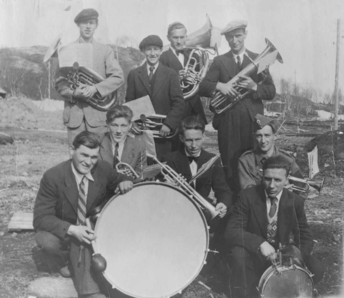 Ni unge menn med diverse messingblåsere og trommer. De er kledt i dress, og utgjør tydeligvis et band. Ingen navn er oppgitt.