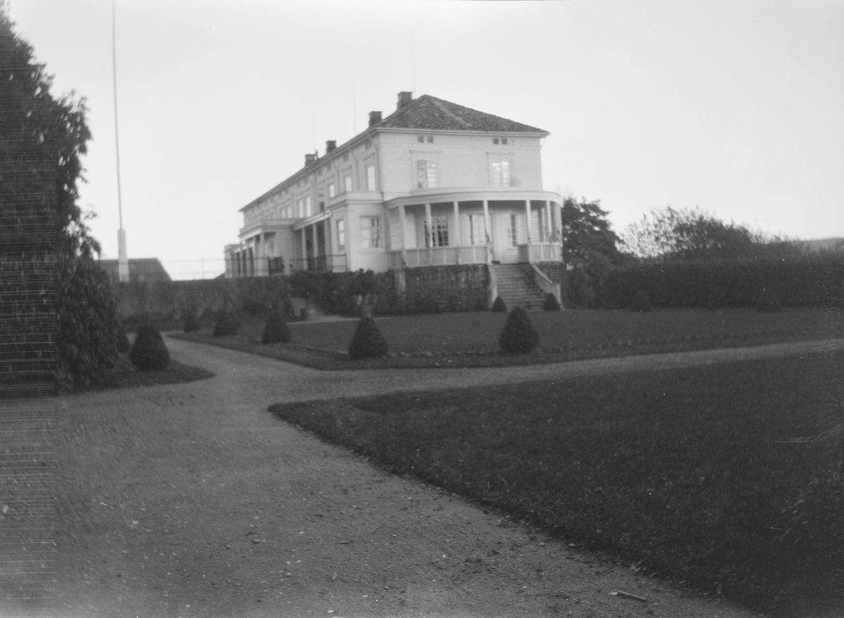 Hovedbygningen på Linderud Gård sett fra siden. Gangstier og friserte busker og hekker sees i front.