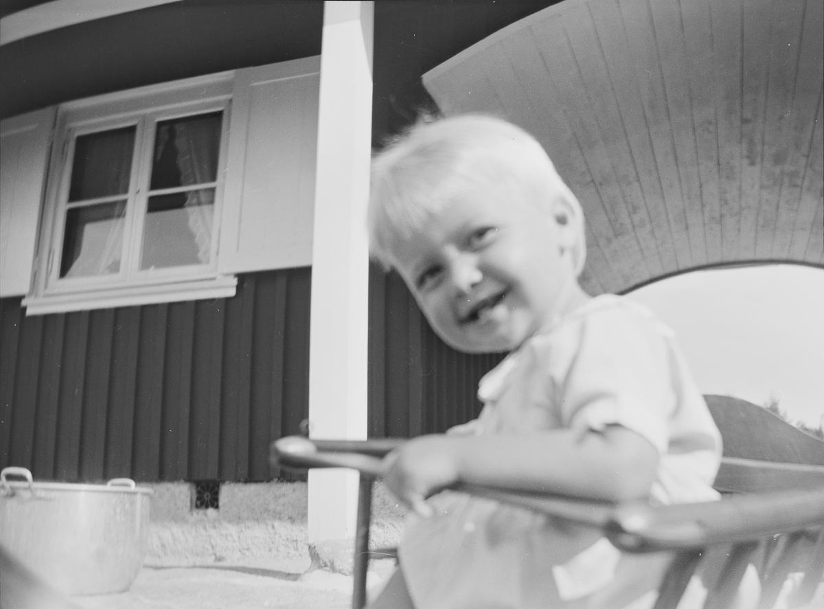 """En liten gutt, """"Lillefar"""", sitter i en barnestol, og smiler til fotografen, foran et hus som består av to deler. De to delene har felles tak, en portal utgjør skillet."""