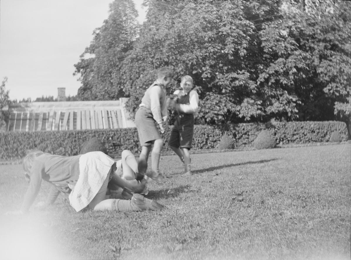 Fire barn, to gutter og to jenter leker på plenen mellom verandaen og drivhusene. Det er sommer på Linderud Gård.