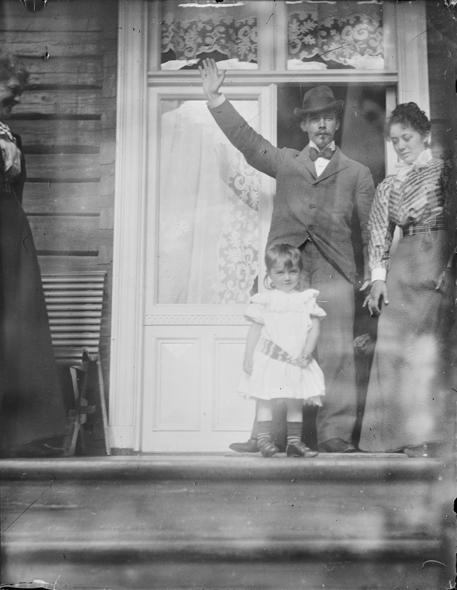 En mann vinker fra verandaen. Ved siden av ham står to kvinner og en jente.