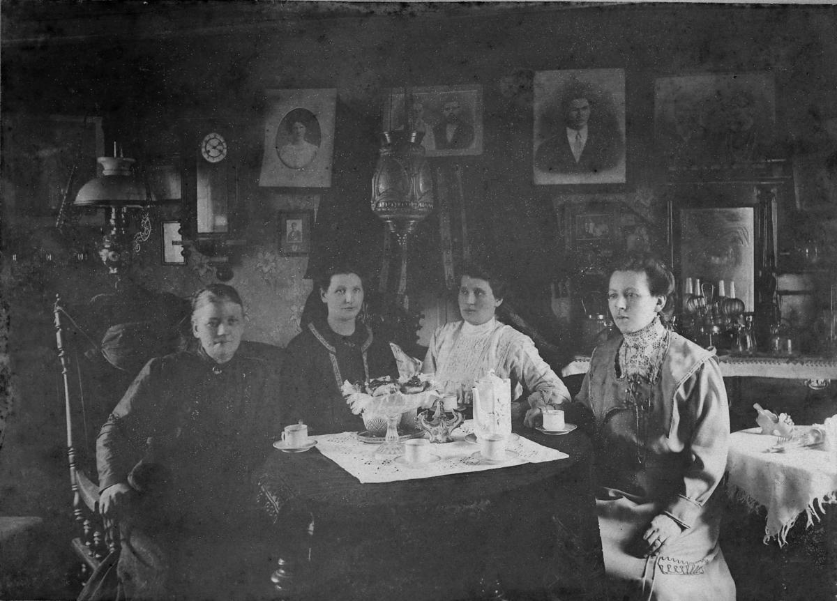 Fire damer sitter i stue til Kima og Peder Lein i Berlevåg.  Fra venstre: Kima Lein, hennes dødre Astrid g. Larsen og Emma g. Mathisen, og svigerdatter Emma Lein f.Wicander. Kvinnene sitter ved et kaffebord. På bordet porselenkopper, kaffekanne og fat med kaker. Emma Lein f. Wicander var født i Syltefjord, dro til Amerika 1901 og giftet seg der med Kimas søn Enok Lein. Familien kom tilbake og bosatte seg i Berlevåg/Båtsfjord i 1911.  Kjolen hennes er tydelig fra denne emigrasjonen.