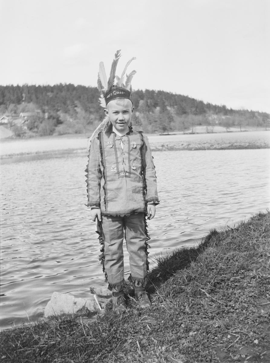 Iacob Ihlen Mathiesen står ved en gresskledd vannkant kledd i et indianerkostyme: bukse overdel og fjærpynt på hodet. I bakgrunnen sees en lav ås med gårdsbebyggelse og en landevei/gårdsvei.