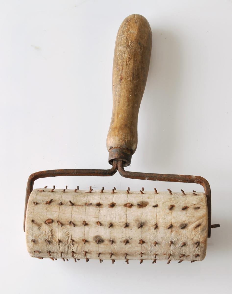 """Form: Trinsa er med bøyde jernpigger, festet til håndtaket med jern. Brukt til flatbrødbaking, for å hindre """"blemmer""""."""