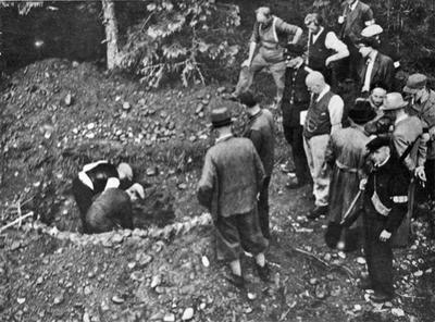 Historisk bilde av folk som graver opp graver etter andre verdenskrig. To menn graver, 14 menn står og ser på.
